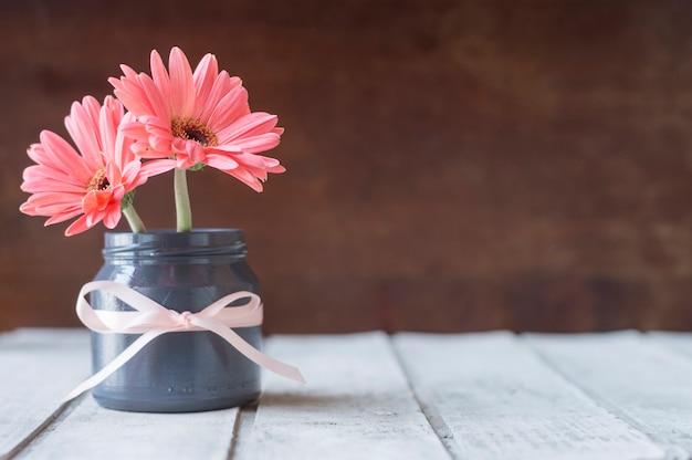 Close-up de vase avec des fleurs et le ruban Photo gratuit