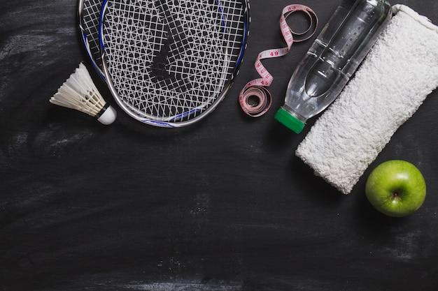 Composition avec la raquette de badminton, une bouteille d'eau et de pomme Photo gratuit