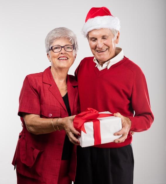 couple de personnes g es en souriant avec un cadeau t l charger des photos gratuitement. Black Bedroom Furniture Sets. Home Design Ideas