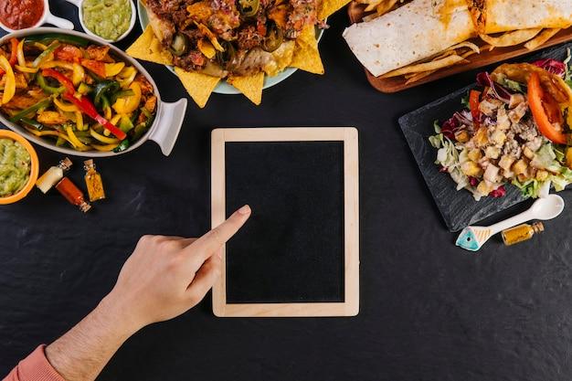 Crop main pointant au tableau près de la nourriture Photo gratuit
