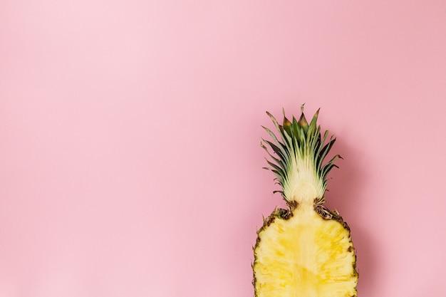 Demi-tranche d'ananas délicieux fraîche appétissant sur fond rose. Vue de dessus. Horizontal. Espace de copie. Conceptuel. Photo gratuit