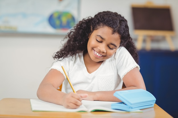 Élève mignon travaillant à son bureau dans une salle de classe
