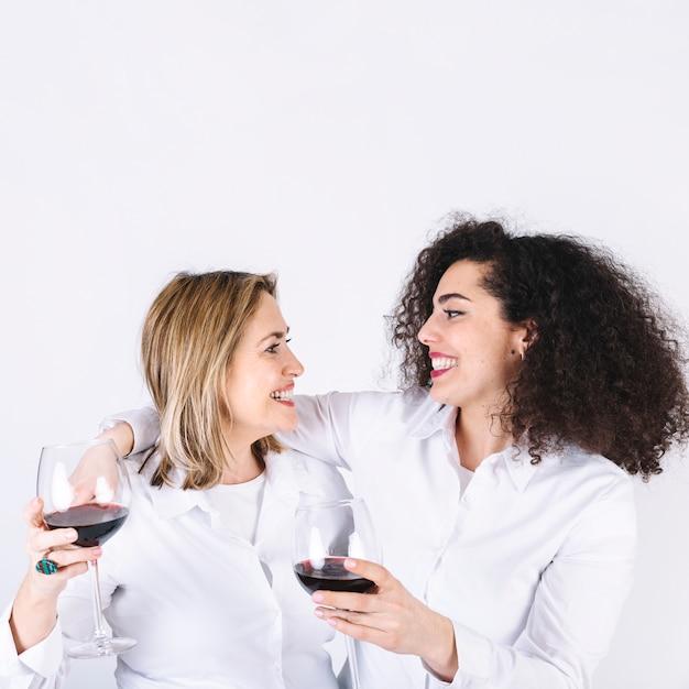 Embrassant les femmes avec des verres à vin Photo gratuit