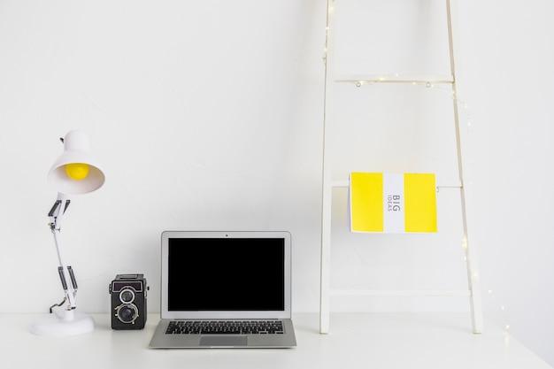Espace de travail élégant de couleur blanche avec échelle et lampe