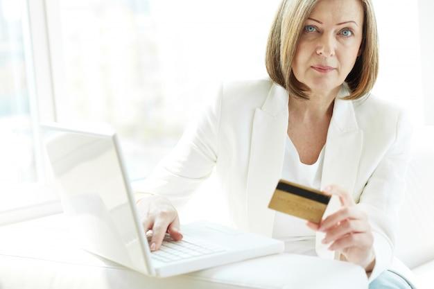 femme avec carte de cr dit et un ordinateur portable pour faire des achats en ligne. Black Bedroom Furniture Sets. Home Design Ideas
