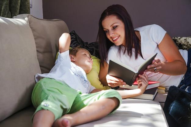 Femme avec fils à lire des livres Photo gratuit