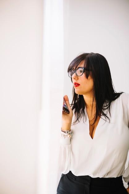 Femme d'affaires confiant posant avec téléphone Photo gratuit