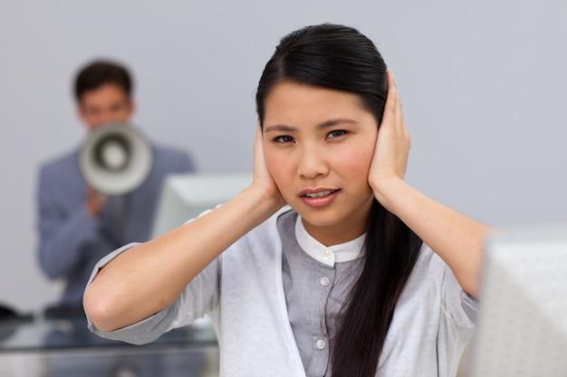 Femme d'affaires couvrant ses oreilles Photo Premium