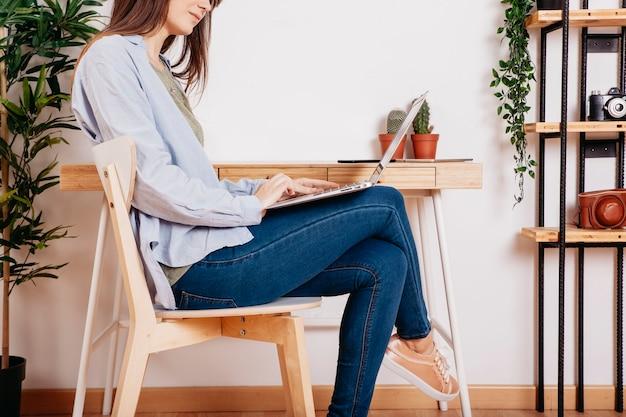 Femme détente avec ordinateur portable à l'espace de travail Photo gratuit