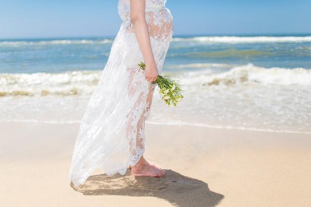 femme enceinte tenant un bouquet sur la plage t l charger des photos gratuitement. Black Bedroom Furniture Sets. Home Design Ideas
