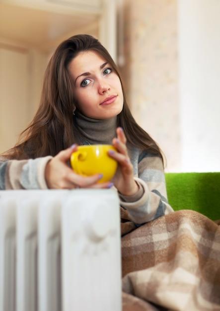 Femme près du chauffe-eau athome Photo gratuit