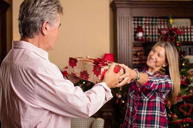 Femme romantique donnant un cadeau son mari - Idee cadeau pour son mari ...