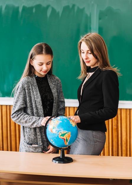 Fille étudiante, apprendre la géographie avec une enseignante Photo gratuit