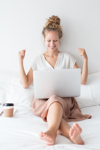 fille gaie travaillant sur ordinateur portable sur le lit