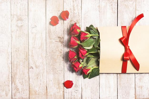 Fleurs dans une enveloppe de papier avec des pétales autour Photo gratuit