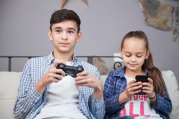 Frères et soeurs souriants avec smartphone et contrôleur Photo gratuit
