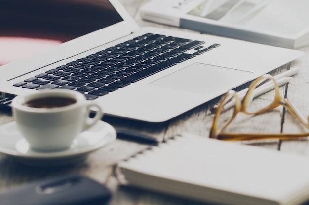 Gros plan de l'espace de travail avec un ordinateur portable créatif moderne, une tasse de café et des crayons. Horizontal avec espace de copie. Photo gratuit