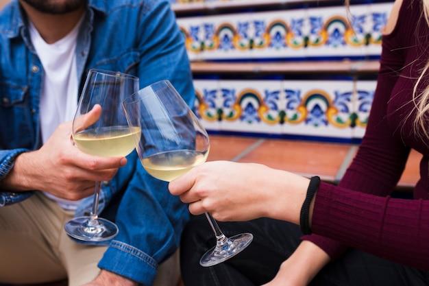 Gros plan des mains d'un jeune couple tinter les verres de vin Photo gratuit