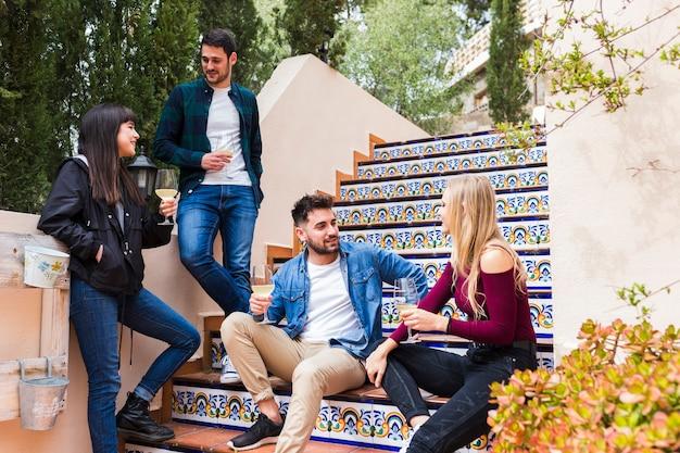 Groupe d'amis avec des verres à vin sur l'escalier Photo gratuit