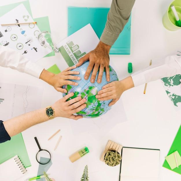 Groupe de gens d'affaires plaçant leurs mains sur le globe Photo gratuit