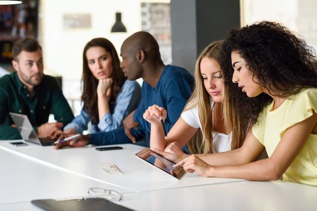 Groupe multiethnique de jeunes étudiant avec un ordinateur portable Photo gratuit
