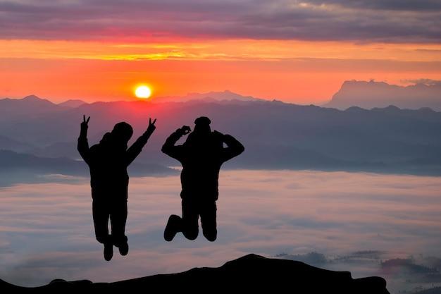 Heureux couple sautant sur la montagne à l\'heure du lever du ...