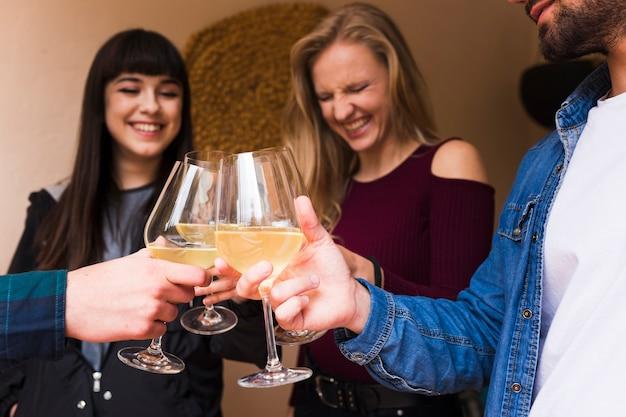 Heureux jeunes amis tenant le verre d'alcool à la main Photo gratuit