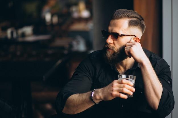 Homme barbu buvant dans un bar Photo gratuit