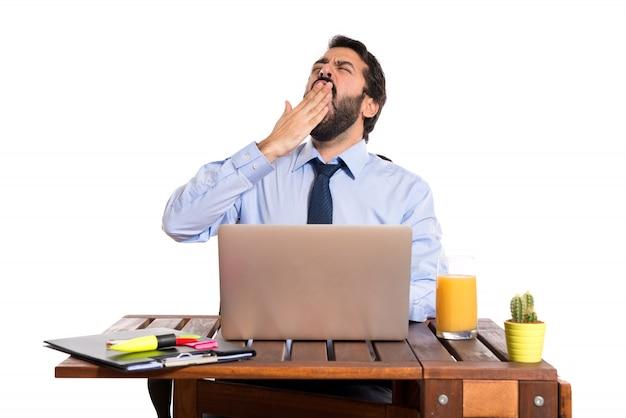 Homme d'affaires bâillant dans son bureau Photo gratuit
