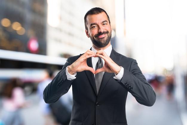 Homme d'affaires faisant un coeur avec ses mains sur un fond non focalisé Photo Premium