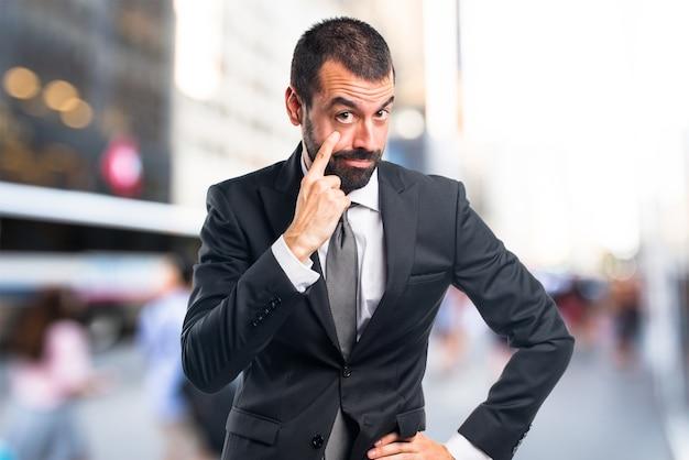Homme d'affaires montrant quelque chose en arrière-plan non focalisé Photo Premium