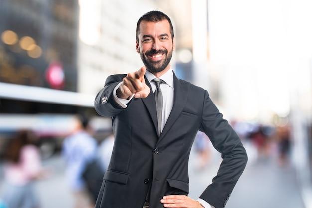 Homme d'affaires pointant vers l'avant en arrière-plan non focalisé Photo Premium