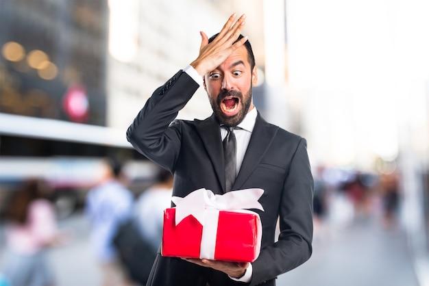 Homme d'affaires tenant un cadeau sur un fond non focalisé Photo Premium