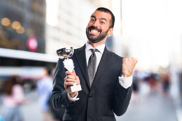 Homme d'affaires tenant un trophée sur un fond non focalisé Photo Premium