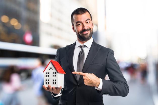 Homme d'affaires tenant une petite maison en arrière-plan non focalisé Photo Premium