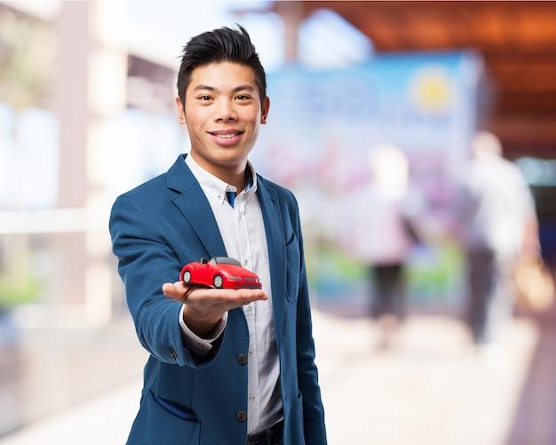 homme souriant tout en maintenant une voiture de jouet rouge t l charger des photos gratuitement. Black Bedroom Furniture Sets. Home Design Ideas