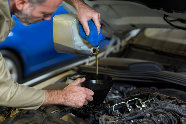 huile coulée Mechanic dans le moteur de voiture Photo gratuit