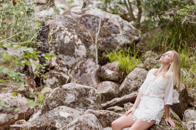 Jeune femme assise sur les pierres et levant les yeux Photo gratuit