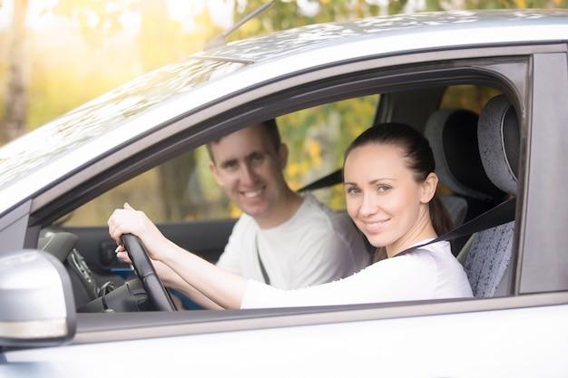 Jeune femme conduisant, un homme assis près de la voiture Photo gratuit