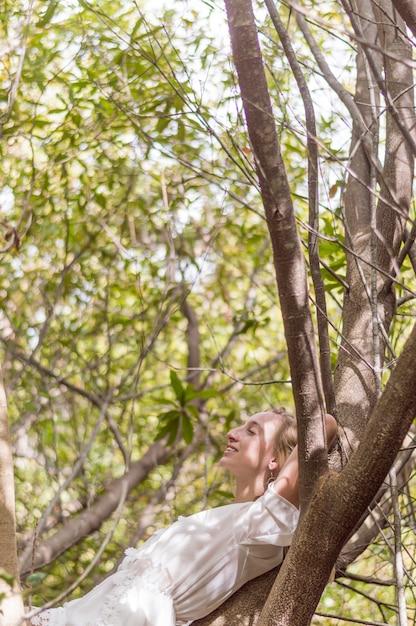 Jeune femme couchée sur un arbre et repos Photo gratuit