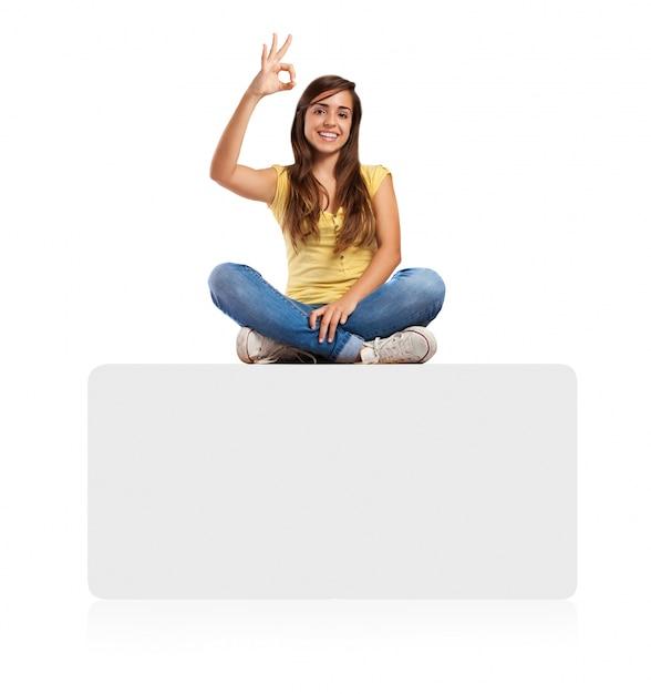 jeune femme faisant signe d 39 approbation assis sur une banni re t l charger des photos gratuitement. Black Bedroom Furniture Sets. Home Design Ideas