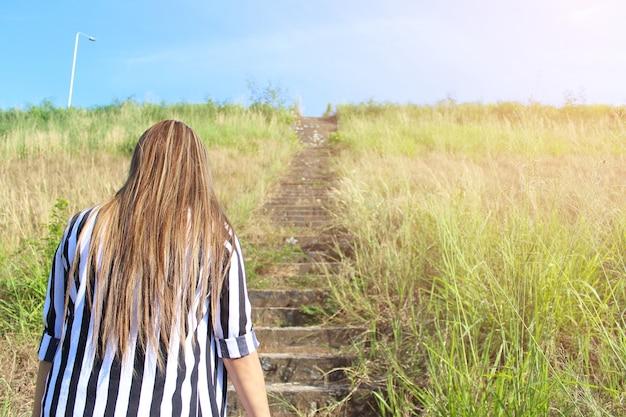 Jeune femme marchant dans le champ vers le soleil Photo gratuit