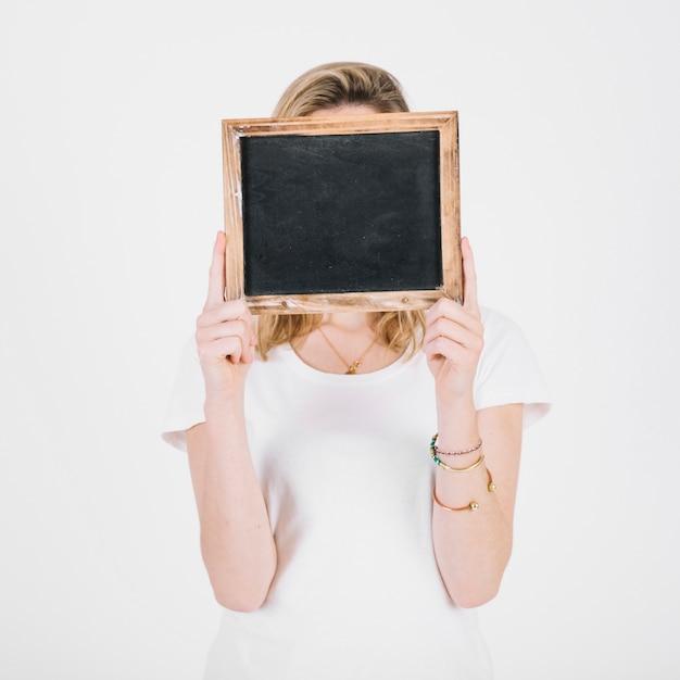 Jeune femme se cachant le visage derrière le tableau Photo gratuit