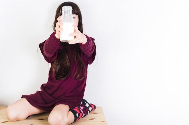 Jeune fille assise sur un bureau en bois montrant une bouteille de