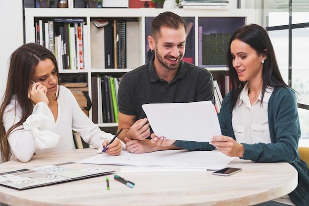 Joyeuse équipe de bureau faisant de la paperasse Photo gratuit