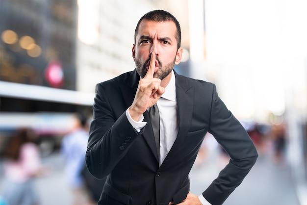 L'homme d'affaires fait un geste silencieux sur un fondement non focalisé Photo Premium