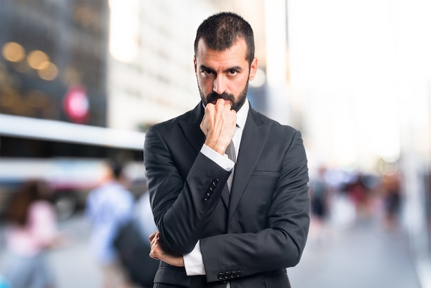 L'homme d'affaires pensant à un contexte non focalisé Photo Premium