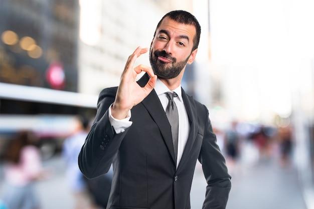 L'homme d'affaires signe OK sur un fond de figure non focalisé Photo Premium