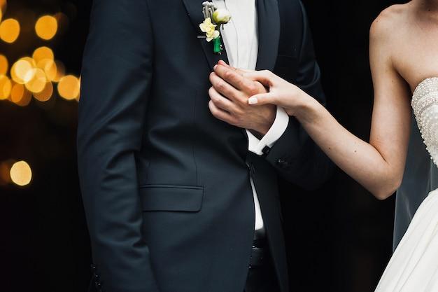 La mariée tient la main du marié pendant qu'ils se tiennent à l'extérieur Photo gratuit