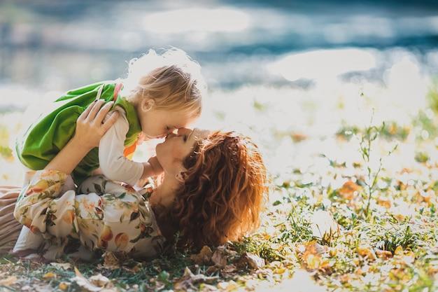 La mère et la fille se trouvent sur l'herbe Photo gratuit